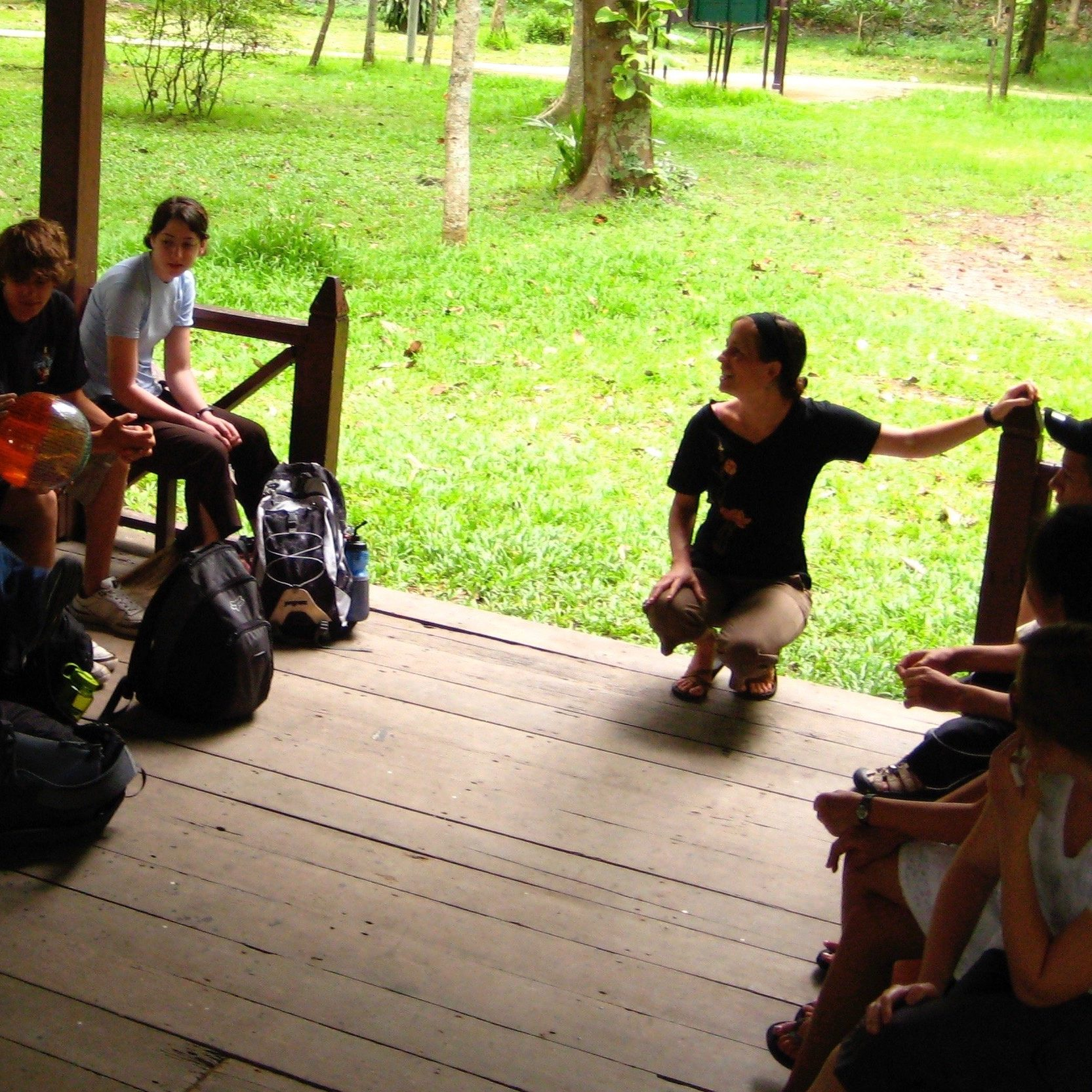 Jane Sarouhan facilitating a group discussion with students inspired to engage life, inside an open-air structure in Thailand
